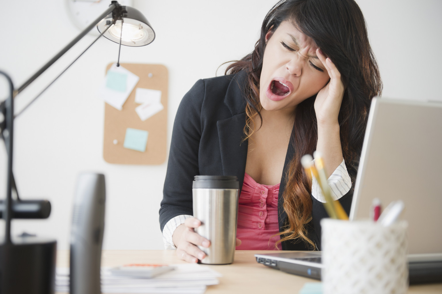 Pacific Islander businesswoman yawning at desk